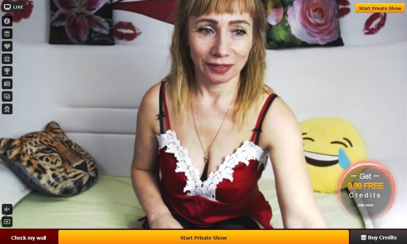 An older blonbe woman with a revealing red cammy with white lace on LiveJasmin.com